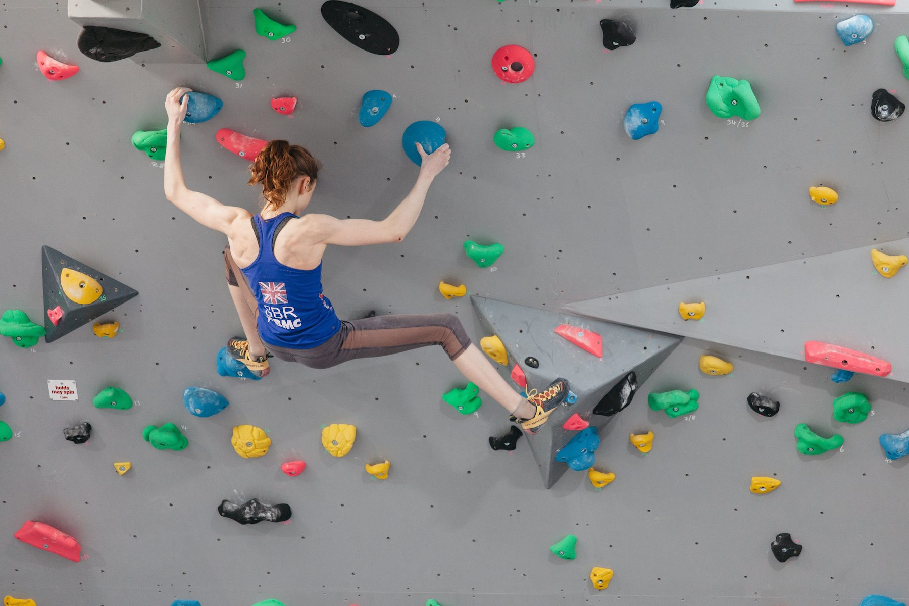 Lady on a boulder wall holding onto blue handholds