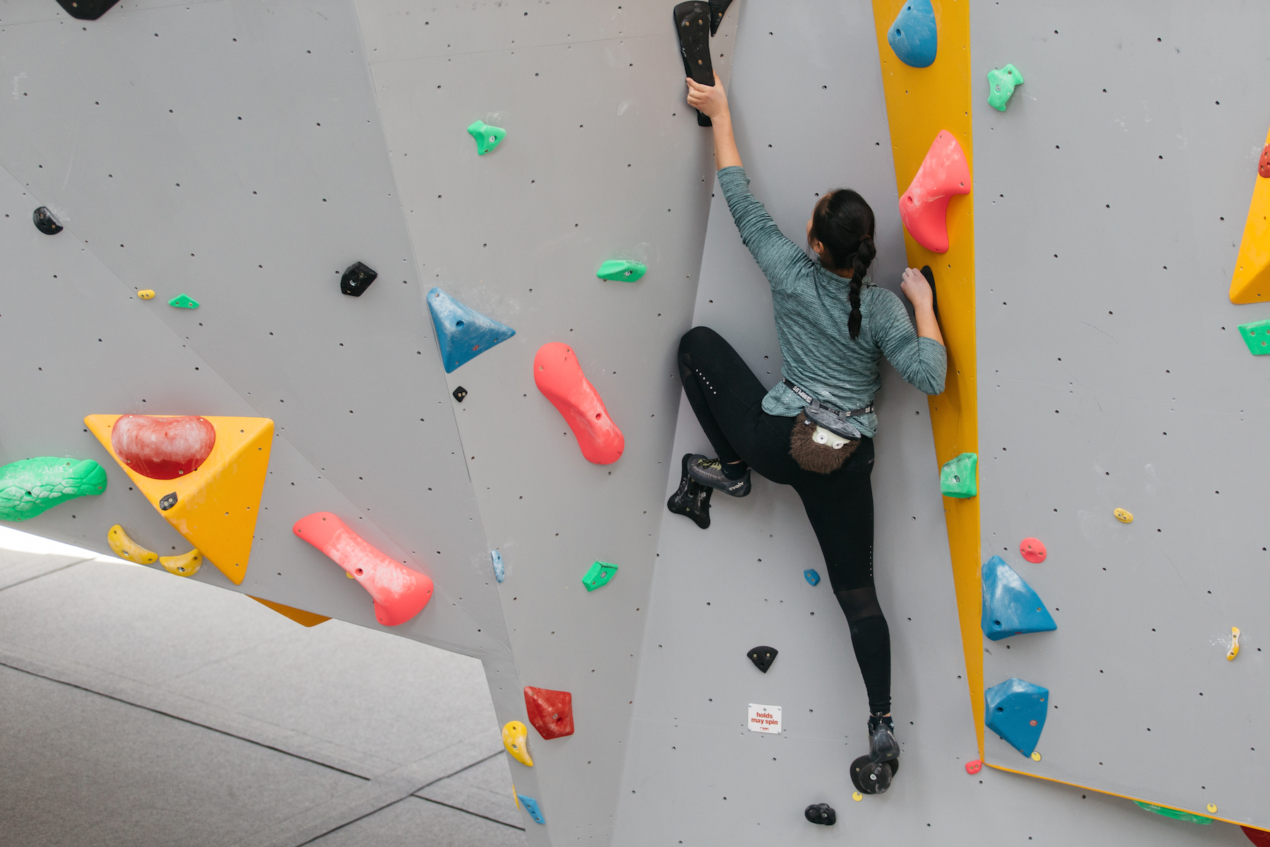Lady climbing on black holds with a high left foot